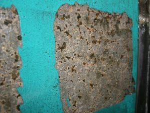Sanierte Schadstellen in der Behälterwand des Monolithen mit zugelassenen Materialien, mehrere Schichten/Lagen, hier: Dichtschicht